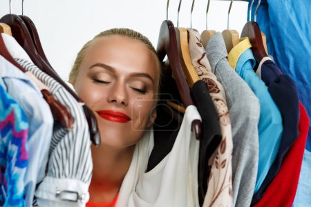 Photo for Beautiful smiling blonde woman standing inside wardrobe rack full of clothes happy to have it. Shopping and consumerism or stylist concept. Nothing to wear and hard to decide concept - Royalty Free Image