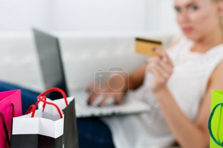 Blond woman making purchasing via internet paying credit card