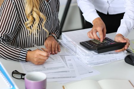 Two female accountants counting on calculator