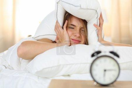Photo pour Jeune femme blonde magnifique couché dans son lit, souffrant de son réveil, couvrant la tête et les oreilles avec oreiller faire visage désagréable. Début réveille-toi, ne pas avoir assez de sommeil, concept de travail continu - image libre de droit