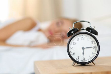 Alarm clock standing on bedside table going to ring early mornin