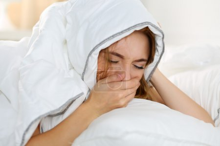Sick young woman lying in bed suffering with cold