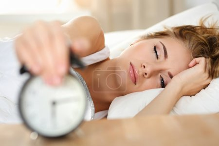 Sleepy young woman portrait with one opened eye trying kill alar