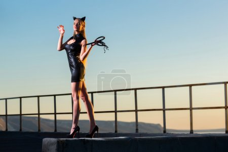 Woman on the roof in a cat costume with a whip