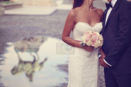 Photo pour Mariée et marié tenant la main dans la ville - image libre de droit
