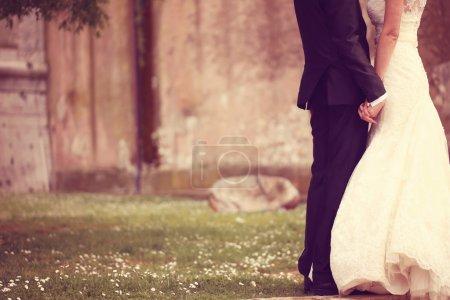 Photo pour Gros plan d'une mariée et d'un marié tenant la main - image libre de droit