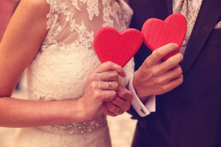 Photo for Bride and groom holding red hearts - Royalty Free Image