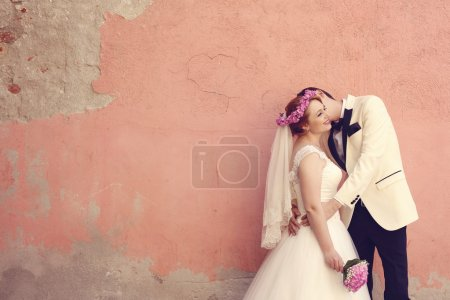 Bride and groom embracing near wall