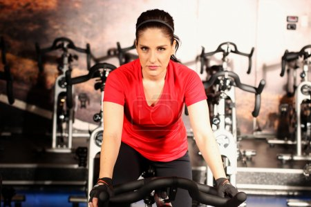 Photo pour Jeunes femmes athlétiques, pédaler sur une salle de fitness vélos d'intérieur - image libre de droit