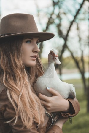 Girl in brown hat keeps white duck on her hands. Portrait of a women with a bird.