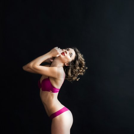 portrait of a young curly girl with dark red lips  with manicure  in underwear