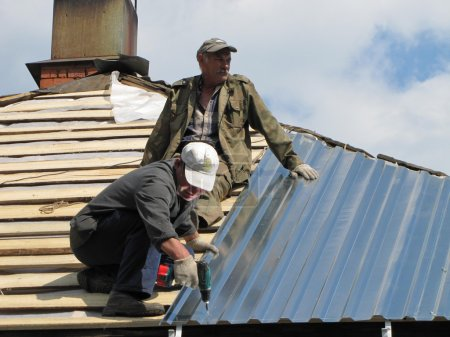 Two workers install roof