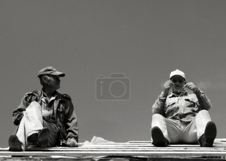 Two workers on wooden roof