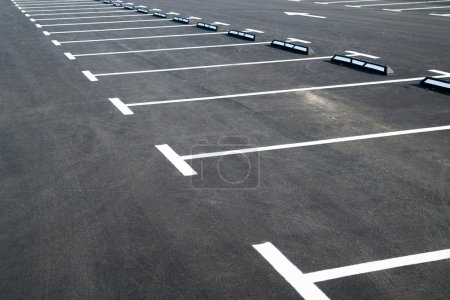 Markings on asphalt pavement indicating parking spaces