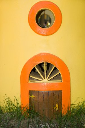 The little door and round window in a yellow wall