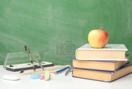 Photo pour Préparer des fournitures pour l'école sur la table à côté de la planche à craie - image libre de droit