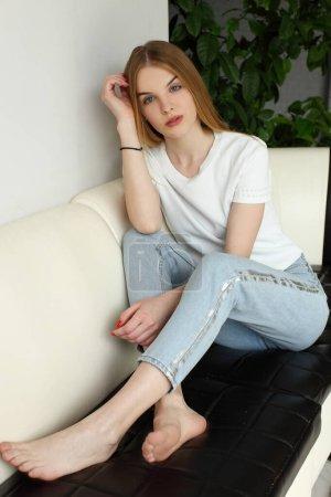 Retrato de una chica relajándose en un sofá después del trabajo en casa sentada en un sofá en la sala de estar en casa con una cálida luz del atardecer