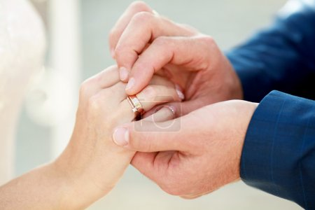 Groom is putting on a ring on bride's finger