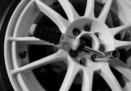 Photo for Tubular screw socket inside the lug pattern of sport car wheel - Royalty Free Image