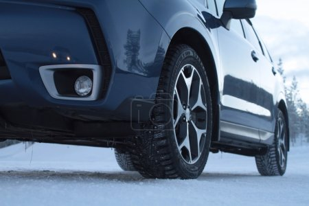 Studded winter tires on car at snow road