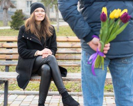 Photo pour Jeune femme s'assoit sur un banc et regarde l'homme debout à côté d'elle, l'homme qui lui donne un bouquet de tulipes - image libre de droit