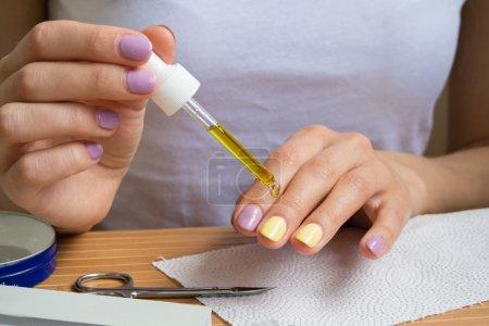 Photo pour Mains de femmes avec brillant vernis à ongles est appliqué l'huile pour cuticules. Une fille assise à une table en bois avec des outils de manucure. - image libre de droit