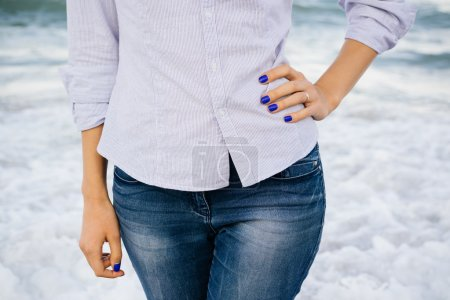 Woman in jeans and shirt standing in the sea foam on the beach