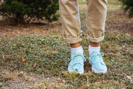 Female feet in beige pants and a turquoise sneakers standing on