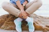 Žena v béžové kalhoty a džínové košili a tyrkysové tenisky si
