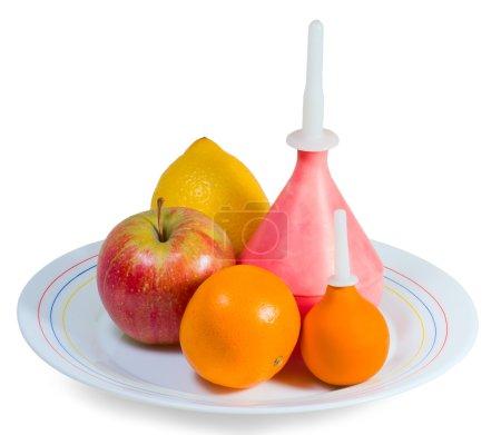 Photo pour Deux lavements, pomme, citron et orange sur une assiette isolée sur blanc - image libre de droit
