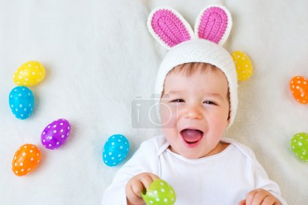 Baby boy in bunny hat lying on green blanket with easter eggs