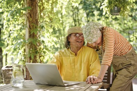 Senior couple outdoors with a laptop