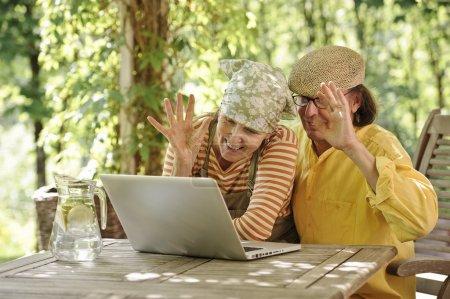 Foto de Pareja de la tercera edad al aire libre con un ordenador portátil, Están mirando a la computadora. Posiblemente tener una videollamada inalámbrica con nietos. Hay un fondo soleado de árboles y arbustos - Imagen libre de derechos
