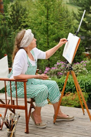 Photo for Senior woman painting outdoors. She sits in a canvas chair in front of the easel. The day is overcast giving a soft light - Royalty Free Image