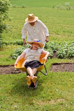 seniors having fun with wheelbarrow