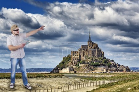 Man with guide book in a hand with Mont Saint-Michel, Lower Normandy, France in background