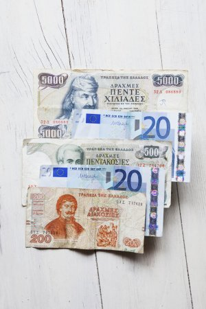 Dinero griego, dracma sobre la mesa con euro