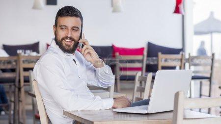 businessman talking on phone in restaurant