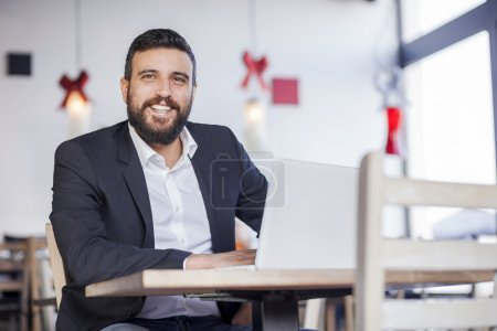 businessman working on laptop in restaurant