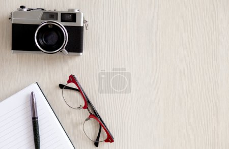 Notebook, pen, glasses and old camera