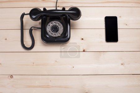 Photo pour Vieux téléphone noir rétro et nouveau téléphone portable sur panneau en bois, vue de dessus - image libre de droit