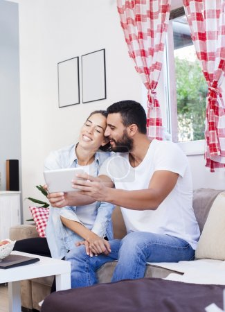 couple using tablet on sofa