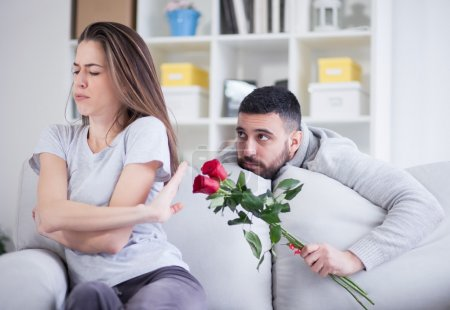 man gives flower to angry girlfriend