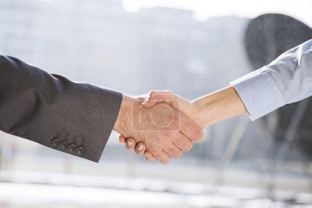 Business handshake between woman and man