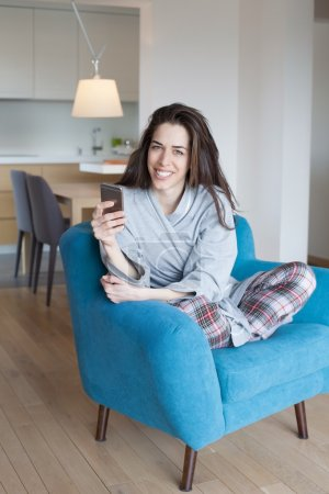 Woman in sofa and using phone