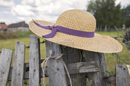 Summer hat hanging on fence
