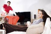 woman sitting at couch watching TV