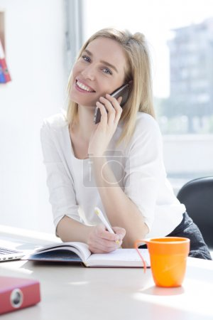 Beautiful young business woman in office talking on phone
