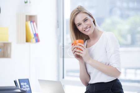 Beautiful Blond Business woman in Office drink Coffee
