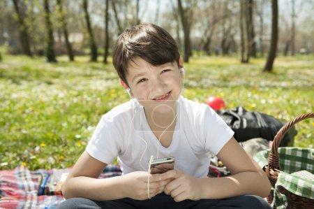 Boy listening to music in park